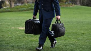 A military aide carries the presidents nuclear football