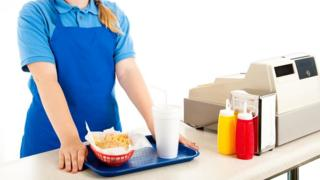 Teenage cashier serving fast food in a restaurant (posed image)