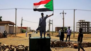 One sudanese protester stand ontop barricade for Khartoum on Wednesday
