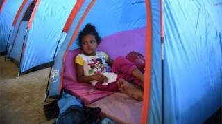 migrant child rests in tent