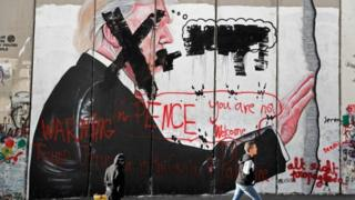 "Palestinian children walk past vandalised graffiti depicting US President Donald Trump and slogans saying US Vice-President Mike Pence is ""not welcome"" in Bethlehem, West Bank, 7 December 2017"
