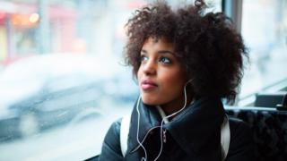 woman listening to headphones on train