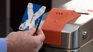 Close up of Michael Matheson, Transport Secretary, using a Scotrail card on the subway