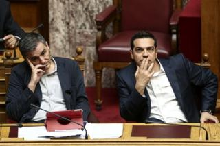 Greek Prime Minister Alexis Tsipras, right, and Finance Minister Euclid Tsakalotos, attend a parliamentary session in Athens, 22 May