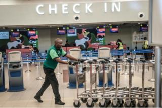 A man moves luggage carts inside the Jomo Kenyatta International Airport in Nairobi, Kenya.