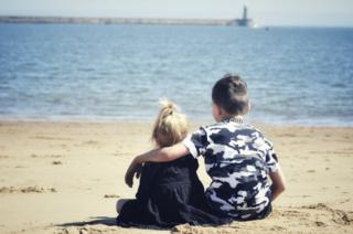 in_pictures Two young children on a beach facing out to sea
