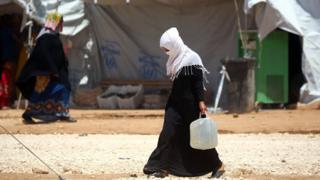 Pengungsi perempuan Suriah membawa air di kamp al-Mabrouka di desa Ras al-Ain di perbatasan Turki-Suriah.