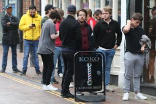 Men queue on the street to enter a Barbers