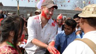 Prince Harry is smeared with powder paint during a Hindu festival