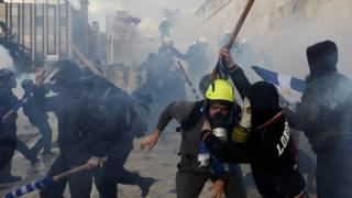 Protesters clash with police officers during a demonstration against the agreement reached by Greece and Macedonia to resolve a name dispute