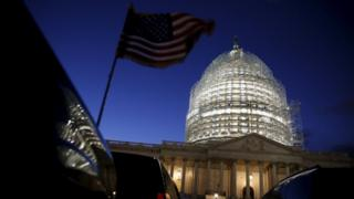 A U.S. flag on a vehicle flutters as the sun sets behind the U.S. Capitol dome in the hours before President Barack Obama delivers the State of the Union address to a joint session of Congress