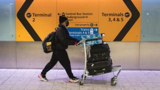 Passenger with mask at Heathrow Airport departures
