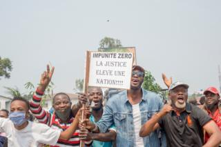 Protesters, including many motorbike-taxi drivers, hold placards while protesting and facing the police around parliament on for the second consecutive day in Kinshasa, DR Congo - 24 June 2020