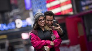A couple takes a photograph of themselves in Times Square, March 1, 2017 in New York City.