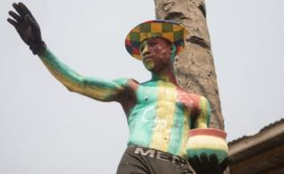 "A Togolese man with body paint in the colours of the national flag and the letter C92 referring to the return to the 1992 Constitution in Togo and for the departure of the current president, watch a protest rally by women marching against Togo""s president in the capital Lome on January 20, 2018."