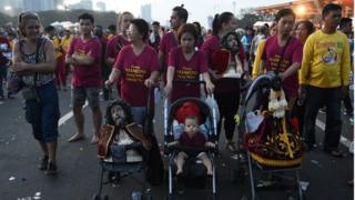 Filipino families push prams, one of which contains a child and two others replicas of the statue. Manila, Philippines. 9 January 2017.