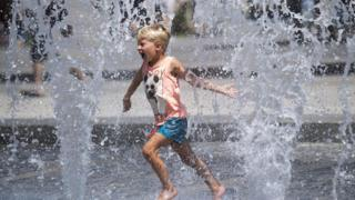 A little boy plays with water-jets in the fountain at the De Ferrari Square on a hot summer day, in Genoa, Italy