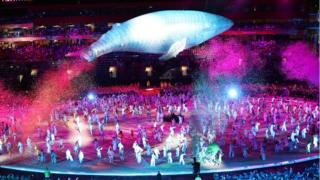 A model of Migaloo, the famous albino humpback whale, appears to jump over all the performers in the final piece of the ceremony.