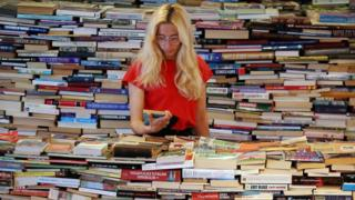 A blonde woman stands in the middle of a huge pile of books.