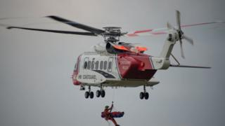 Rescue helicopter winches the injured man