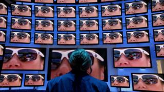 Woman looks at high-definition 3D television screens at Panasonic stand in 2010
