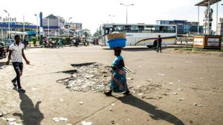 People walk in an empty street in Kinshasa on April 3, 2017 during a general strike called by the opposition