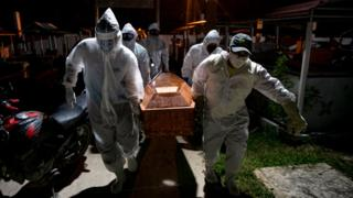 positive people Gravediggers wearing protective clothing carry the coffin of a victim of the coronavirus