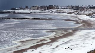 Beach covered in snow with buildings in the distance