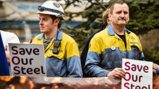 """Two steel workers hold signs saying """"save our steel"""""""
