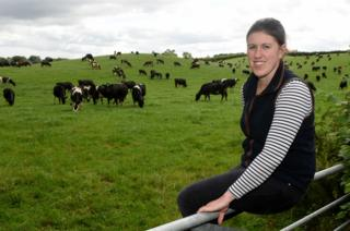 Liz Haines sits on a fence in front of a field