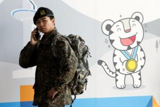 A South Korean soldier uses mobile phone at the 2018 PyeongChang Winter Olympic and Paralympic Games PR booth on January 5, 2018 in Seoul, South Korea