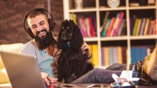 A smiling man wears a headset with his feet up, cradling a dog while he taps on his laptop