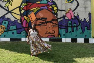 """Brion Gill, also known as Lady Brion, is a member of young Baltimore activists """"Leaders of A Beautiful Struggle,"""" poses for a portrait in front of a mural in Baltimore, Maryland, USA. 30 July 2019."""
