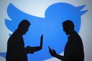 El perfil de dos hombres con lapton y celular frente a un logo de Twitter
