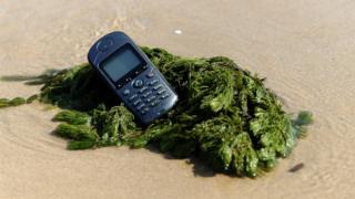 teléfono móvil descatalogado en la orilla de la playa.