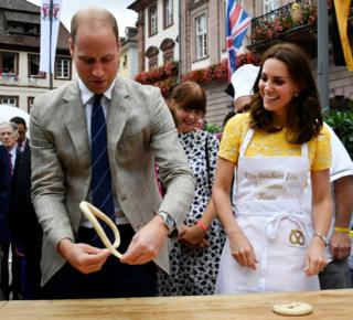 Britain's Prince William, Duke of Cambridge, and his wife Kate, the Duchess of Cambridge, form pastry to pretzels during their visit of the market in the historic centre of southern German town of Heidelberg on 20 July 2017.