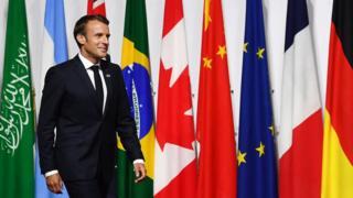 O presidente francês Emmanuel Macron passa pelas bandeiras dos países participantes do encontro do G20 em Osaka, no Japão