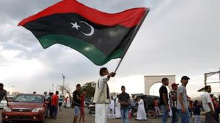 A Libyan man waves his national flag during a demonstration against supporters of the regime of former dictator Muammar Gaddafi in Benghazi