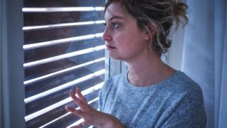 environment Scared woman looking out of the window