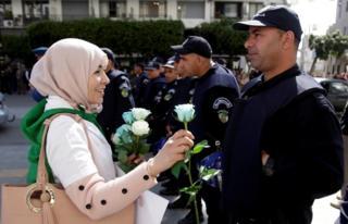 Участница антиправительственной демонстрации в Алжире дарит белую розу полицейскому.