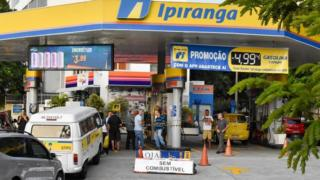 A petrol station in Brazil with people trying to get in. There is black and yellow tape going between the pillars to stop people from driving in.