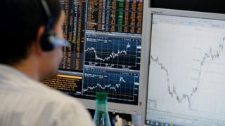 A trader checks his screens at investment bank Saxo Banque in Paris