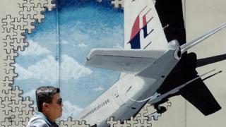 man walking past MH370 memorial