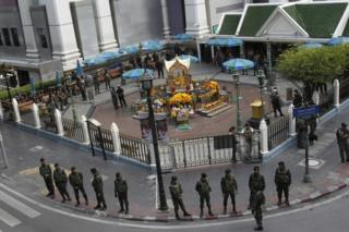 Thai soldiers stand guard outside Erawan Shrine before a key suspect in last month's Bangkok bombing, identified as Adem Karadag, arrives for a reenactment of the August 17 bombing at Bangkok's popular Erawan Shrine Saturday, Sept 26, 2015.