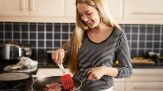 Woman cooking bacon