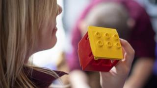 A girl holds a building block to her face