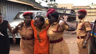 Dkt Nyanzi akisaidiwa kutembea na maafisa wa mahakama