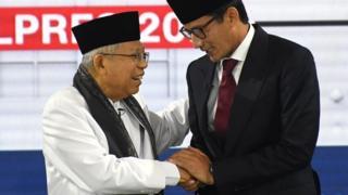 Cawapres nomor urut 01 K.H. Ma'ruf Amin (kiri) berjabat tangan dengan Cawapres nomor urut 02 Sandiaga Uno (kanan) saat mengikuti Debat Capres Putaran Ketiga di Hotel Sultan, Jakarta, Minggu (17/3/2019).