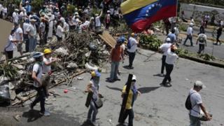 Miembros de la oposición al gobierno de Maduro en una barricada.