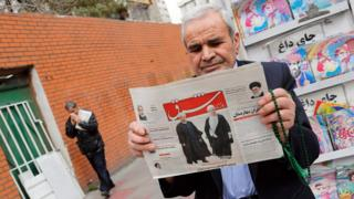 An Iranian man reads a newspaper in Tehran